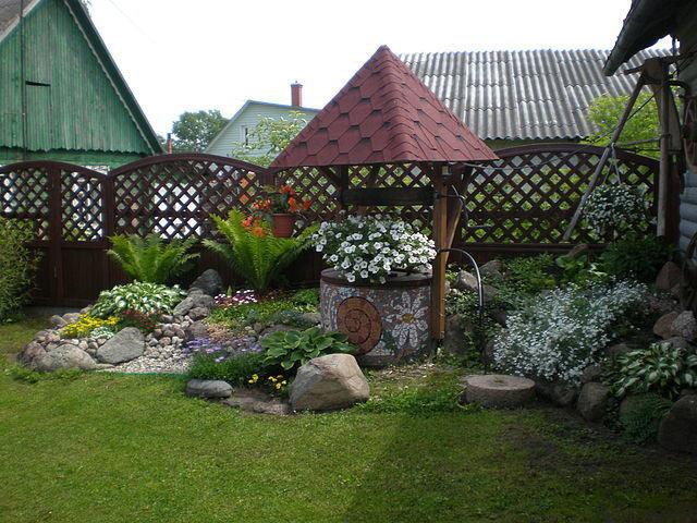 колодец декоративный для ландшафтного дизайна облагороженный камнями и кустами с цветами