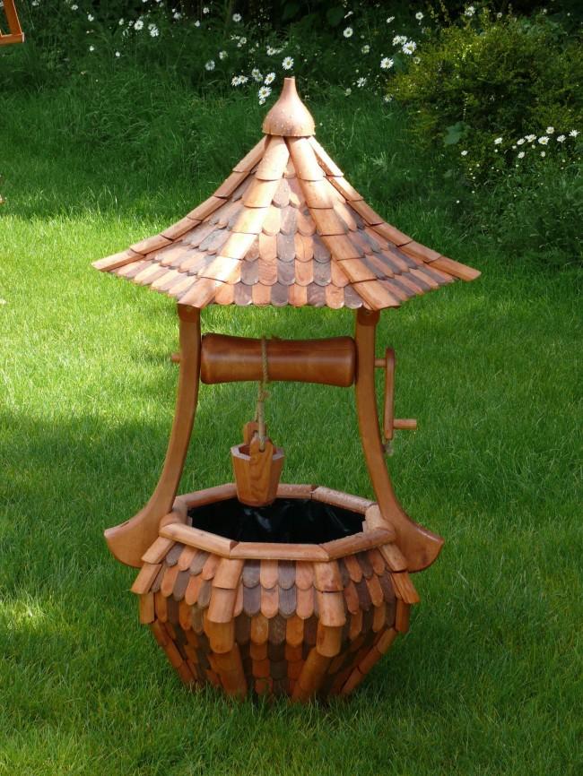маленький декоративный колодец с изогнутой крышей и маленькой бадьей