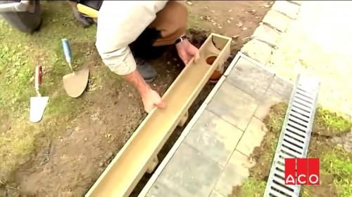 установка первого водоотводного пластикового лотка на бетонное основание возле тротуарной плитки